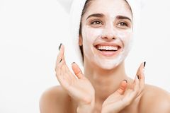 Beauty Skin Care Concept - Beautiful Caucasian Woman Face Portrait applying cream mask on her facial skin white. Background royalty free stock photo