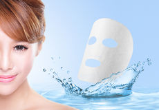 Beauty Skin care concept. Beautiful woman face with Water splashes and cloth facial mask isolated on blue background, asian model Royalty Free Stock Photos