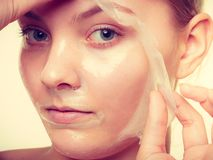 Woman removing facial peel off mask stock photography