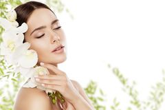 Beauty Skin Care and Face Makeup, Woman Skincare Natural Make Up. Beautiful Model and Orchid Flower, eyes closed royalty free stock photo