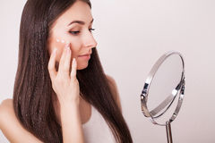 Beauty, skin care and people concept - smiling young woman applying cream to face and looking to mirror at home bathroom Royalty Free Stock Images