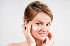 Beauty and skincare concept. Young woman applying moisturizer on face. Royalty Free Stock Image