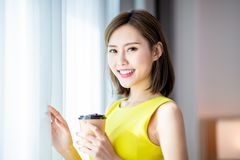 Beauty smile to you with coffee. Beauty asian woman drink coffee and enjoy a wonderful morning in the hotel royalty free stock photography