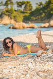Beauty smiling. Beautiful young woman wearing sunglasses and yellow bikini lying on the beach holding her legs and feet up in the air looking at the camera stock images