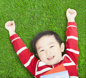 Beauty smiling child boy resting and hand up with books Stock Photos
