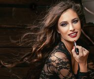 Beauty smiling rich woman in lace with dark red. Lipstick, flying hair close up stock photo