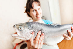 Beauty smiling woman holding raw salmon or trout fish food Royalty Free Stock Images