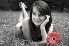 Beauty Smiling Women With Flower. Beauty Smiling Young Women With Red Flower Laying On The Grass Royalty Free Stock Photography