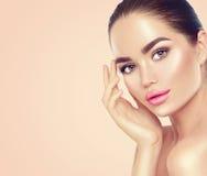 Beauty spa γυναίκα brunette σχετικά με το πρόσωπό της στοκ φωτογραφίες με δικαίωμα ελεύθερης χρήσης