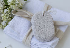 Beauty spa with body care pumice stone on white towels, bath spa Stock Image