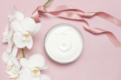 Beauty Spa concept. Opened plastic container with cream and White Phalaenopsis orchid flowers on pink background Flat lay top view stock photo