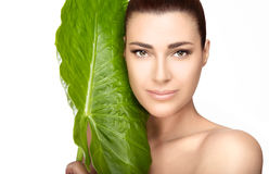 Beauty Spa Girl near Green Leaf over White Background. Beauty and skincare portrait. Beautiful spa girl with the large fresh green leaf of a tropical plant Royalty Free Stock Photo