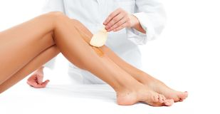 Beauty Spa. Hair removal cosmetology procedure.  Beautician waxing female legs. Beauty Spa. Hair removal cosmetology procedure. Beautician waxing a female leg Royalty Free Stock Photography