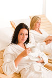 Beauty spa relax two women on sun-beds. Beauty health spa treatment two women relax sun-beds coffee book royalty free stock photos