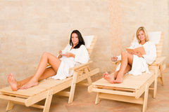 Beauty spa room two women relax sun-beds. Spa luxury relax room two beautiful women lying on sun-beds royalty free stock photography
