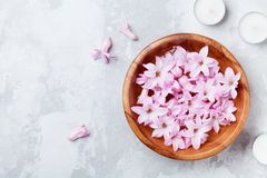 Beauty, spa and wellness composition of perfumed pink flowers water in wooden bowl and candles on stone table. Aromatherapy.