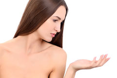 Beauty Spa Woman with perfect skin Portrait. Beautiful Brunette Spa Girl showing empty copy space on the open hand palm Royalty Free Stock Photos