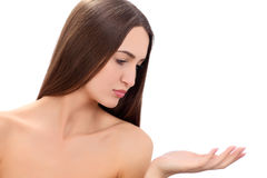 Beauty Spa Woman with perfect skin Portrait. Beautiful Brunette Spa Girl showing empty copy space on the open hand palm Stock Photos