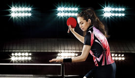 Beauty sporty girl playing table tennis on black background. Portrait Of Young Woman Playing Tennis On Black Background with lights Stock Photos