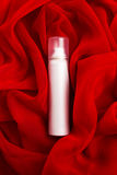 Beauty spray (aerosol) over red cloth background Stock Image