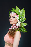 Beauty Spring girl with flowers hair. Beautiful model woman with flowers on her head. The Nature Of Hairstyle. Summer Stock Photo
