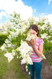 Beauty of springtime without allergy. Girl smelling white syring. Beauty of springtime without allergy. Young teenage girl enjoying of blossoming white syringa Stock Photography
