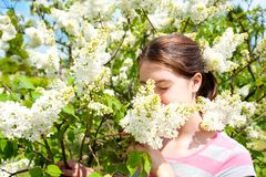 Beauty of springtime without allergy. Girl smelling white syring. Beauty of springtime without allergy. Young teenage girl enjoying of blossoming white syringa Stock Images