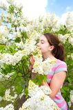 Beauty of springtime without allergy. Girl smelling white syring. Beauty of springtime without allergy. Young teenage girl smelling blossoming white syringa tree Royalty Free Stock Photos