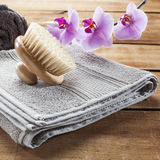 Beauty still-life for skin rejuvenation with softness. Back brush for beauty ritual at spa center with cotton towel and orchid flowers for femininity Royalty Free Stock Photo