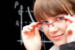 Beauty student and blackboard. Pretty student touching her glasses and blackboard against white background Stock Photography