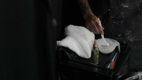 Beauty Studio. The hairdresser stylist is stirring the hair dye using a brush. Balayazh. Slow motion stock footage