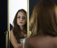 A beauty studio picture of a young woman looking in a mirror, wh Royalty Free Stock Photos