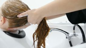 Beauty studio. Washing woman hair with shampoo, Make-up and beauty salon. Close up hand of hairdresser washing hair on. Head. Concept of hair care stock footage