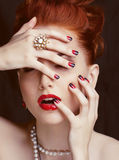 Beauty stylish redhead woman with hairstyle and manicure wearing jewelry pearl close up Stock Images