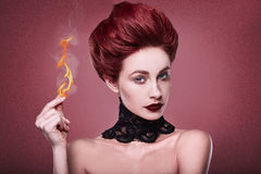 Beauty stylish redhead woman with hairstyle and necklace jewelry. Beauty stylish redhead woman with hairstyle and wearing necklace jewelry with fire on her Royalty Free Stock Photo