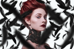 Beauty stylish redhead woman with hairstyle and wearing necklace jewelry. With falling raven feathers in studio Stock Image