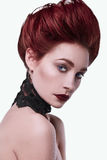Beauty stylish redhead woman with hairstyle and wearing necklace jewelry. In studio Stock Photography