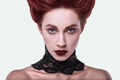 Beauty stylish redhead woman with hairstyle and wearing necklace jewelry. In studio stock photo