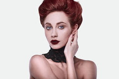 Beauty stylish redhead woman with hairstyle and wearing necklace jewelry. In studio Stock Image
