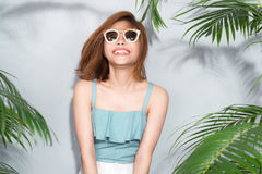 Beauty summer. Beautiful asian woman between palm leaves. Royalty Free Stock Image