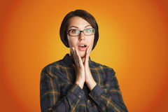 Beauty surprised woman on orange background Stock Photos