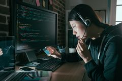 Hacker wearing headset and holding credit card. Beauty sweet hacker wearing headset and holding credit card doing telecommunications fraud in order to getting stock image
