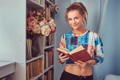 A beauty tattoed girl in casual clothes. Young tattooed girl standing near a bookcase read a book at home stock photography