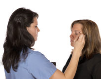 Beauty technician applying makeup on client Stock Image