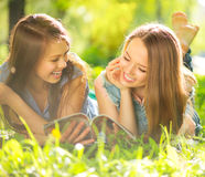 Beauty teen girls reading magazine outdoors Royalty Free Stock Image