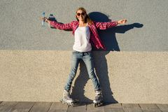 A beauty teen model girl, shod in rollerblades. Holding a water bottle. Sports, health and active leisure Stock Images
