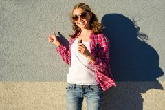 Beauty teen model girl shows thumbs up. With chocolate on a gray wall background Royalty Free Stock Photos