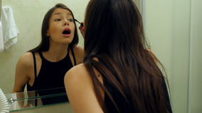 Beauty teenage girl applying mascara make-up very fast because she is late stock video footage