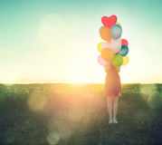 Beauty teenage girl on summer field with colorful air balloons stock images