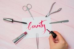 Beauty text. Font of lettering word on white paper with red ink by calligrapher. Cosmetic products frame. Graphic design stock image